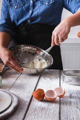 Woman baker stir dough with eggs and flour