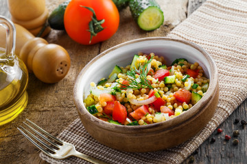 Healthy salad for breakfast made of couscous, tomatoes, cucumber and onion on a table. Traditional Israeli Ptitim meal. Moroccan cuisine food.