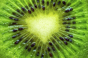 Bright green background of one slice piece of juicy kiwi fruit close up. Healthy food background.