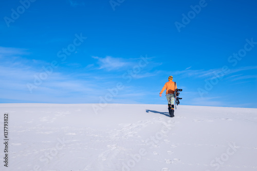Guy in funny cap with a snowboard goes up the sand dune