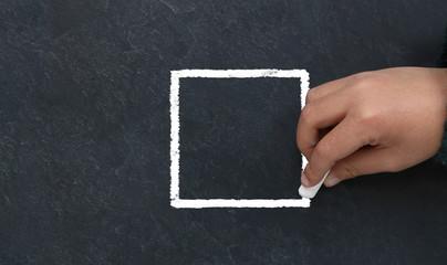 Enfant dessinant un carré à la craie sur une ardoise