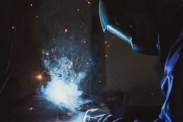 Industrial workshop man welding round pipe on a metal work table, colorful smoke, sparks and reflections