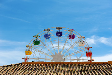 Brown roof, ferris wheel and blue sky