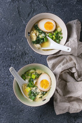 Two bowls with asian style soup with scrambled eggs, half of marinated egg, spring onion, spinach served with white spoons and textile over black texture concrete background. Top view with space