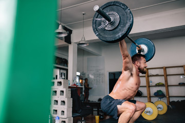 Strong athlete exercising with heavy weights