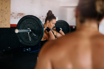Female bodybuilder doing weightlifting exercise in gym