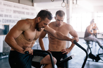 Muscular athlete doing intense workout on gym bike with coach