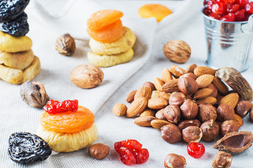 Mix of dried fruits and nuts, almonds, hazelnuts, dried cherries, dried apricots, figs and prunes on white wooden background. Healthy and wholesome food. The concept of natural organic food, diet.