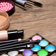 Set of basic make-up products on wooden surface