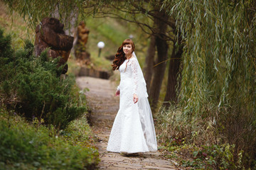 Beautiful bride in a wedding dress and veil lace in nature. Beautiful girl model in white wedding dress. Cute lady outdoors. Portrait of a woman in a park. Woman with hairstyle