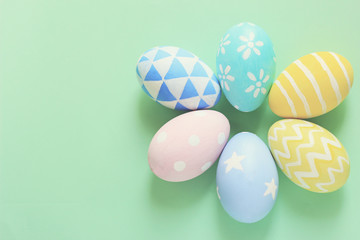 Pastel and colorful easter eggs with copy space on green background.