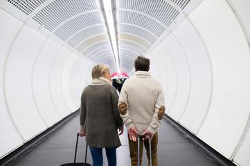 Senior couple in hallway of subway pulling trolley luggage.