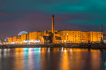 The pump house and warehouses of the historic Albert Dock complex are reflected in Canning Dock in Liverpool, UK