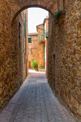 Mooi smal steegje met traditionele historische huizen in de stad Pienza
