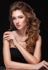 Beautiful elegant woman in pearl necklace, long curly tress over black background. Fashion glamour portrait.