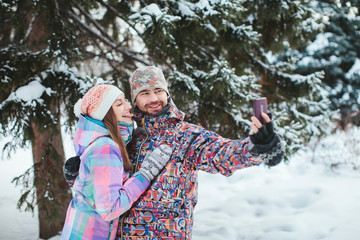 young happy couple making selfie phone in the winter forest