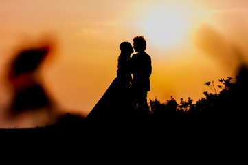 Silhouette of Asian Bride and Groom Standing on Mountain at Sunset