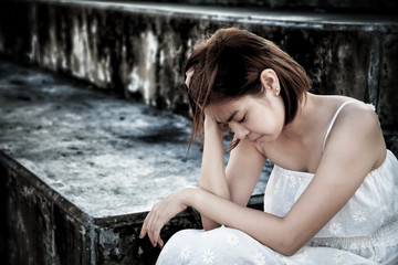 woman in frustrated depressed sitting on stairs, crying and contemplating suicide, in scary abandoned building, Concept of unemployed, sadness, depression, broken heart and human problem in dark tone.