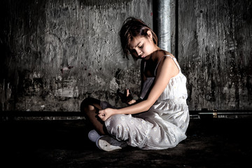 Drug abuse concept., overdose asian female drug addict use syringe injection narcotic to her hand., in scary abandoned building., In dark tone.