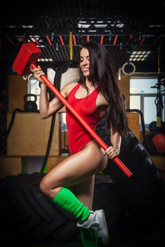 A woman in a red bathing suit. A woman is holding a sledgehammer in his hand. In the gym.