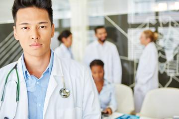Junger asiatischer Arzt vor seinem Team