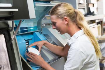 Dental technician puts ceramics implant in milling machine