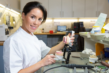 Dental technician holding articulator with prosthesis