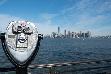 Tower viewer binoculars on a swivel stand next to a railing on the edge of Liberty Island, New York City.  View of Lower Manhattan and New York Harbor from the Statue of Liberty. Bright, sunny day.