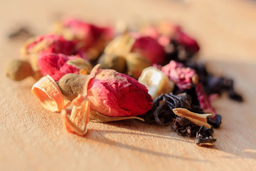 Macro photo of tea with a tea rose. The composition of the heap of tea roses and dried hibiscus flower located on a wooden Board. Black tea with natural rose flower closeup.