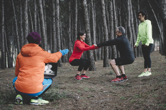 Group of people doing a training in the forest, the personal trainer leads with laptop.