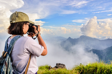 Hiker asian teens girl with digital camera and backpack taking photo beautiful natural of sierra sky clouds and fog during sunset in winter on mountain at Phu Chi Fa Forest Park, Chiang Rai, Thailand