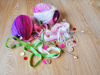 Skeins of thread, buttons and measuring tape on wooden background.