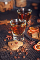 Whiskey or liqueur, cookies, spices and decorations on wooden background.