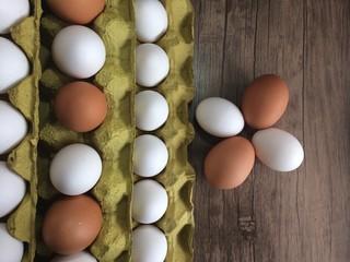 ahşap zemin üzerinde, kolilerdeki sarı ve beyaz yumurtalar.