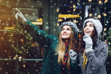 Outdoor waist up portrait of two young beautiful fashionable happy smiling surprised girls posing on street. Models looking up, wearing stylish winter clothes. Snowfall, festive christmas background