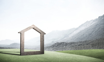 Conceptual image of concrete home sign on hill and natural lands