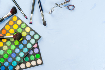 Set for makeup - brush, mascara, eye shadow, on a light blue stone concrete table top view copy space