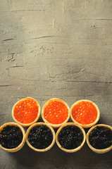 Black and red caviar tartlets, appetizer canapes on gray background, top view
