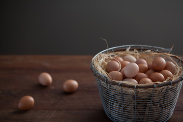 Metal Wire Basket of Fresh Farm Chicken Eggs on a Rustic Brown Wooden Farm Table