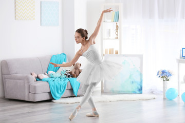 Young beautiful ballerina dancing in room