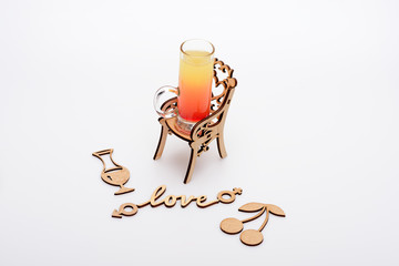 alcohol cocktail in glass on little decorative chair, love inscription