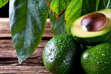 Fresh organic avocado on old wooden table. The composition of pictures in close-up.