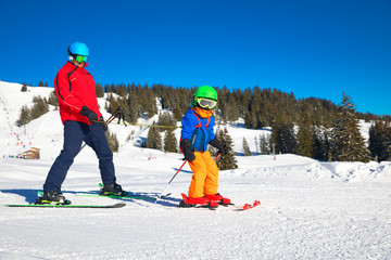 Happy little boy learning skiing with his father in Alps