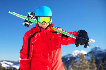 Young attractive caucasian skier with skies on the ski slope in Alps