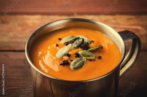 Foto: Roasted pumpkin soup in metal mug with seeds and smoked paprika ...