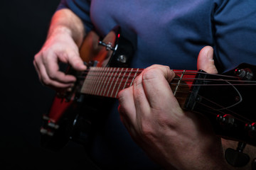 Guitarist playing close-up on electric guitar on a black background