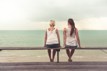 Two young women sitting together and looking into the distance on beach. Concept for togetherness
