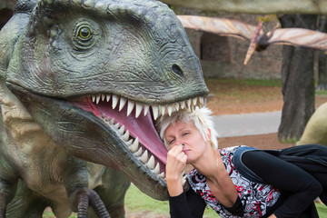 Belgrade, Serbia - October 05, 2014: Young woman put her head into the stinky mouth of a dinosaur in the dino park, Belgrade, Serbia