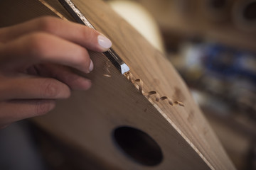 close up on female hands wood carving a tambur musical instrument