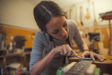woman luthier is using a tool to grind a classic guitar fretboard in her musical instrument workshop